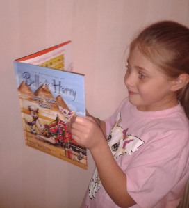 "Abby reading her favorite Bella & Harry book - ""Let's Visit Cairo!"""